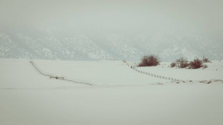 A crop irrigation system sits on a snow-covered field in winter. Fog blankets the mountainside, as wind blowing snow causes near whiteout conditions in a rural Idaho location.