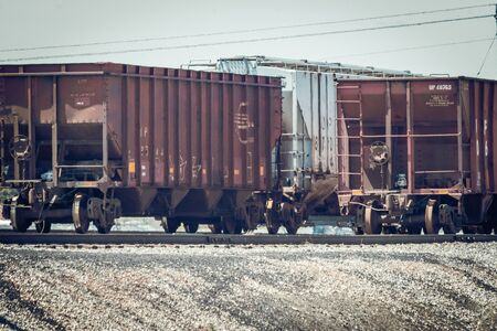 Rusty grain hopper train cars sit on railroad tracks awaiting pickup from a cargo train to be taken to their destination.