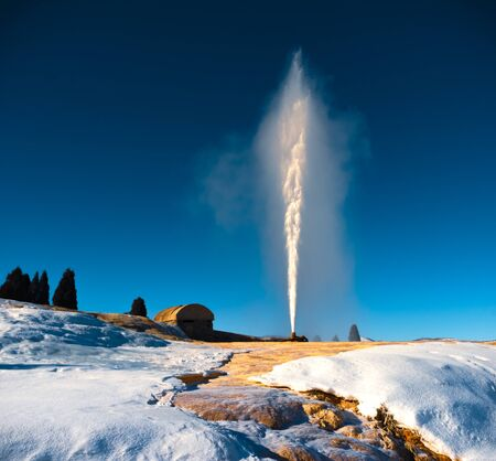 The Soda Springs Geyser blowing off some steam on a very cold Winter day. The bright white water stands out against a vivid blue sky and the frozen landscape that surrounds. Stock Photo