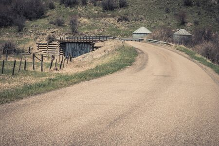 A country road crosses an interesting bridge in Idaho. The bridge becomes a narrow road with metal siding underneath and wooden retaining walls. The metal siding makes one wonder what it's covering up under the bridge.