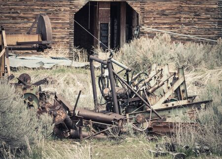An old grain elevator in Soda Springs, ID sits abandoned next to railroad tracks, surrounded by overgrown landscape and a junkyard of rusty vintage farm equipment and machinery parts. Stock Photo
