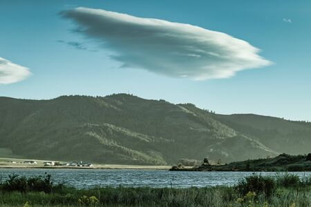 A large swirling cloud hovers above the  blue Alexander Reservoir and forest covered mountains in Idaho.
