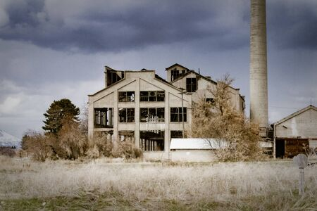 The Franklin County Sugar Factory near Preston, Idaho sits abandoned against a dark and cloudy sky. Stock Photo