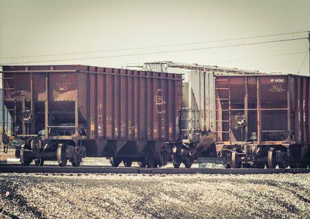 A vintage edit of train cars sitting on railroad tracks. Stock Photo