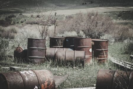 A bunch of old rusty barrels sit abandoned in a field. Some bullet holes can be seen from people shooting at them. The overall image gives off a vintage urbex vibe.