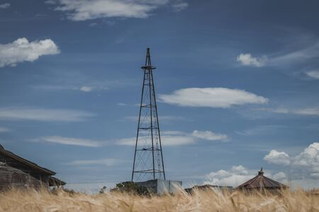 A vintage broken windmill tower sits on an abandoned rural farm and golden grain field.
