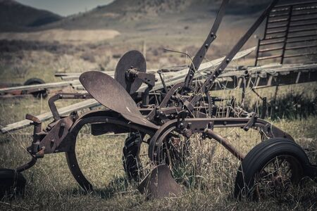 An old vintage horse-drawn plow sits abandoned in a  grassy field surrounded by old farming machinery and equipment.