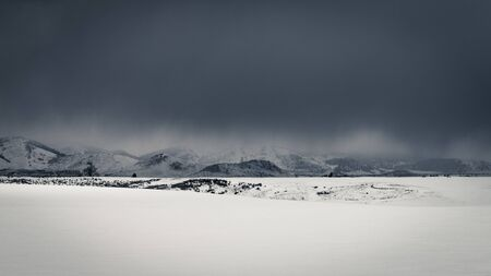 Dark clouds give way to snowfall in a rural snow-covered field during an Idaho Winter. Stock Photo