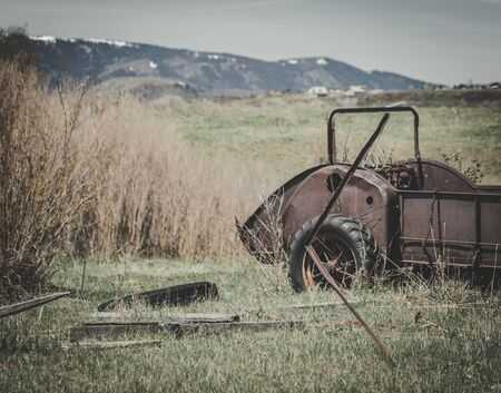 An old vintage hay baler cart sits abandoned on a farm surrounded by a grassy field, old junk and dried brush.