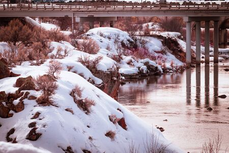 Sun sets and creates colorful reflections in the still water below the bridge at the Bear River Dam. Snow and drided sagebrush cover the rocky cliffs surrounding the low-lying river below.