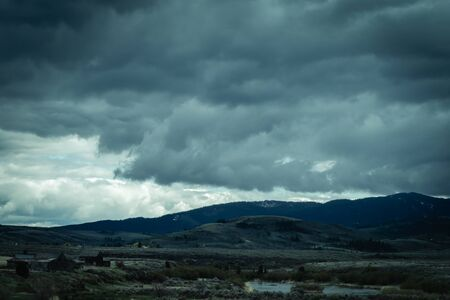 The storm clouds at this high elevation always seem low enough to reach out and touch them, as seen in this photo of evening storm clouds over a rural valley.