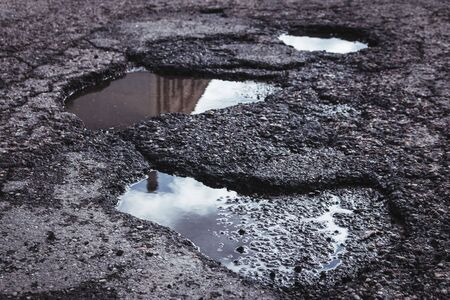 A building can be seen as a reflection in these pot holes in the road.