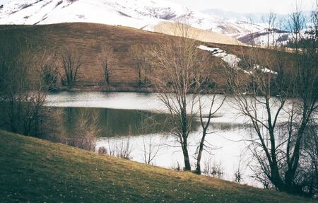 A river divides Winter and Spring, with one side a green grass-covered river bank, surrounded by dark bare trees, and the other, snow-covered mountains. Stock Photo