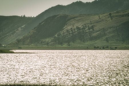 The sparkling water of the Alexander Reservoir meets rolling green hills.