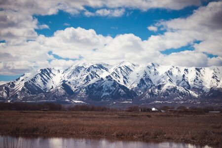 A snow-covered mountain in Logan, Utah sits above a drab Spring farm and field, with a pond reflecting in the foreground.