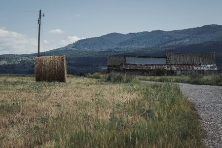 An abandoned vintage barn sits in a field next to a rolled bale of hay and wilderness mountains. Stock Photo