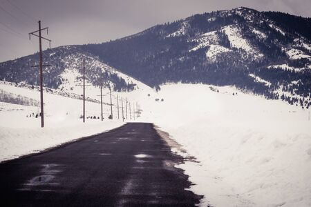 A road to nowhere ends at a scenic winter view of the mountainside and snow-covered field. The road is wet with puddles and bordered by electric poles.