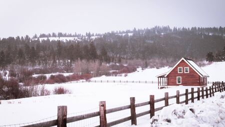 A little red farm cabin sits in a snow-covered field, surrounded by mountain scenery.