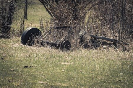 An old rusty and broken truck axle sits in a grassy field with the remains of vintage farm machinery.