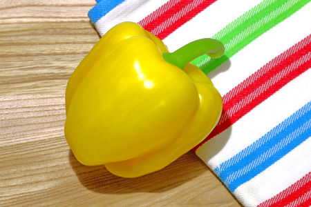 dishtowel: Yellow sweet bell pepper on wooden board slicing breadboard with colorful dishtowel
