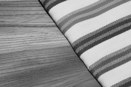 dishtowel: Black and white photo of dishtowel tablecloth on wooden table with copyspace