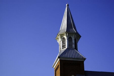 A church steeple at sunset, with a bright blue sky background Stock Photo