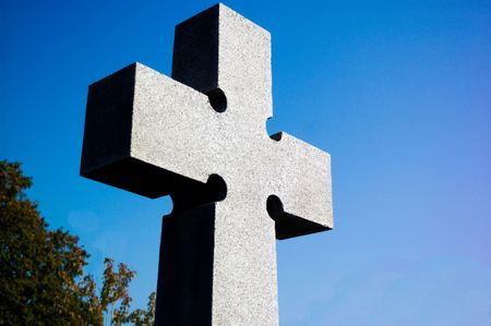 A gray stone cross in a graveyard