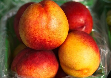 A carton of peaches at the market Stock Photo