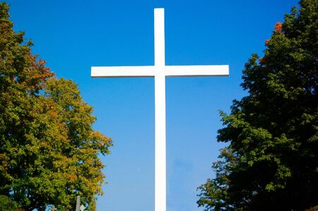 Large white wooden cross, with a bright blue sky