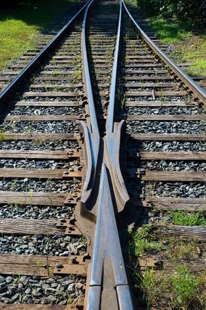 Two railroad tracks merging together in the sun Stock Photo