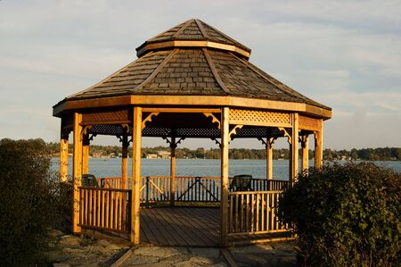 A wooden gazebo sits on a lakeshore, at sunset