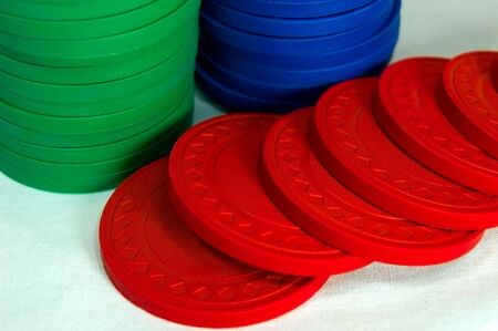 Three colors of poker chips on a table Stock Photo