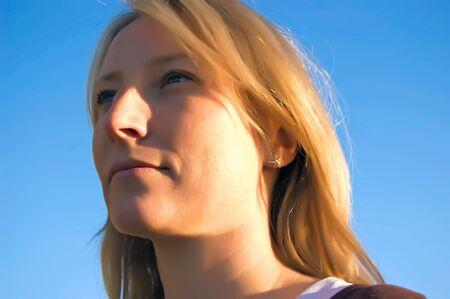 A pretty woman with blue eyes looks skyward