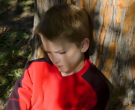 A boy sits under a tree in the shade Stock Photo - 3673169
