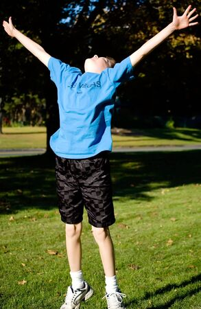 A boy jumps for joy in the park Stock Photo - 3686053