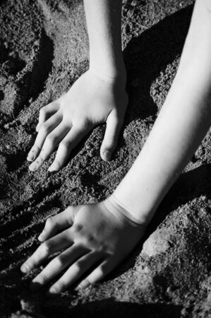 Hands playing in the sand