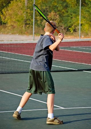 A teenage boy playing tennis, shwing his forehand
