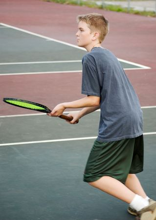 Teenage boy playing tennis, approaching the net photo