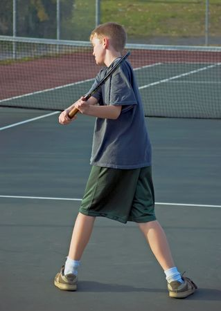 A teenage boy playing tennis - showing his backhand Stock Photo - 3702714