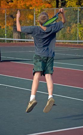Teenage Boy Playing Tennis, Serving Stock Photo