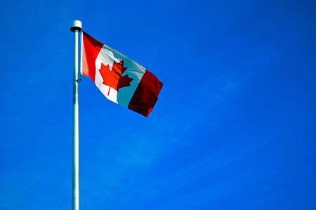 A Canadian Flag on a bright blue sky