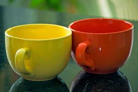 A yellow and orange coffee mug sit on a marble countertop