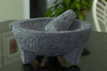 A granite mortar and pestle on a Marble Countertop