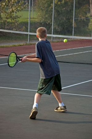 A teenage boy prepares to backhand the tennis ball