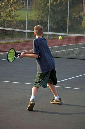 A teenage boy prepares to backhand the tennis ball