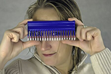 A young woman with wet hair looks through a comb
