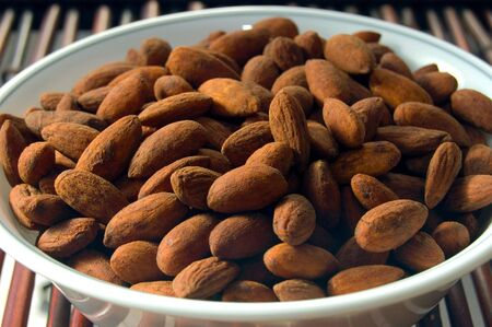 A bowl of salted almonds in the sunlight