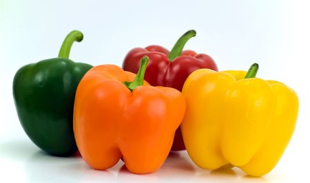 Four different colors of peppers isolated on white