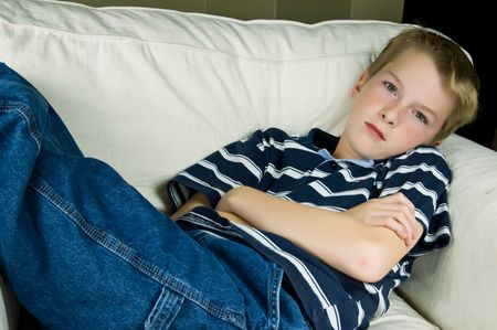 A teenage boy relaxes in a comfy white chair Stock Photo