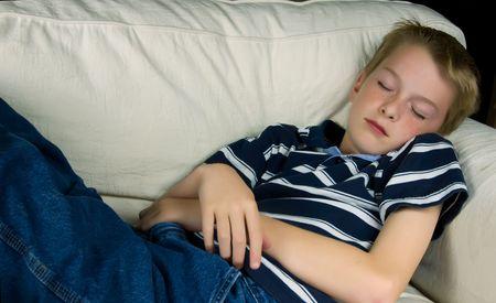 A teenage boy sleeping in a comfy chair